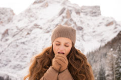 Woman warming hands with breathe among snow-capped mountains Stock Photos