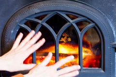 Woman warming hands at fire fireplace interior. Royalty Free Stock Photo