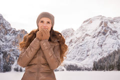 Woman warming hands outdoors among snow-capped mountains Stock Photography