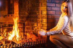 Woman warming hands up at fireplace. Winter home. Stock Photography