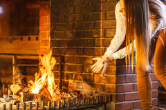 Woman warming hands up at fireplace. Winter home. Stock Image