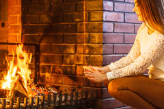 Woman warming hands up at fireplace. Winter home. Royalty Free Stock Image