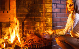 Woman warming hands up at fireplace. Winter home. Royalty Free Stock Photos
