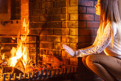 Woman warming hands up at fireplace. Winter home. Stock Photo