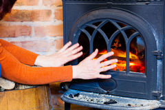 Woman warming her hands at fire fireplace interior. Heating. Stock Photo