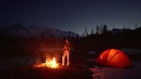 Woman warming up in a camping by the fire in mountains. At night.There is forest and snowcapped mountains on the background stock footage