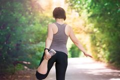 Woman warming up before jogging, outdoor exercise. Healthy lifestyle concept stock image