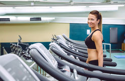 Woman warming up over treadmill in training session Stock Photos