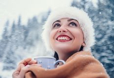 Woman warms with cup of hot tea in snow forest Royalty Free Stock Image
