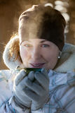 Woman warms frozen hands wearing gloves, close up facial portrait Royalty Free Stock Images