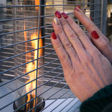 Woman warms hands on a modern street fire. Stock Photography