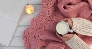 Woman warms hands on a mug of hot milk. A woman warms hands on a mug of hot milk - A woman relaxes with a cup of hot milk in a cozy ambient with a book candle stock video footage