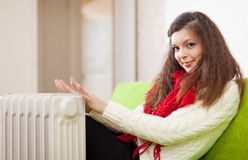 Woman warms hands near calorifer at home Royalty Free Stock Photography