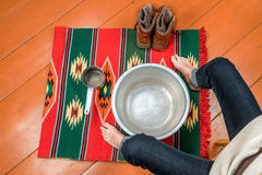 Woman warms her feet in a basin of water Stock Photos