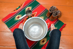 Woman warms her feet in a basin of water Royalty Free Stock Photos