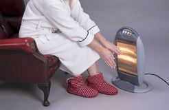 Woman warms her hands on an electric fire Royalty Free Stock Photos