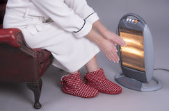 Woman warms her hands on an electric fire Stock Images