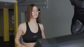 A woman warms her muscles on a cardio simulator before training. stock footage