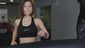 A woman warms her muscles on a cardio simulator before training. stock video footage