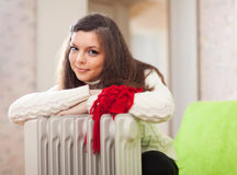 Woman  warms near warm heater Royalty Free Stock Images