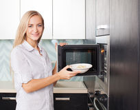 Woman warms up food in the microwave Royalty Free Stock Images