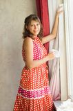 The woman warms a window. The woman seals up a window paper strips stock photography
