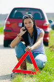 Woman with a warning. Young Woman with a warning triangle in case of breakdown Stock Image