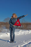 Woman with a warning triangle. In sunny winter day above broken car Stock Photos