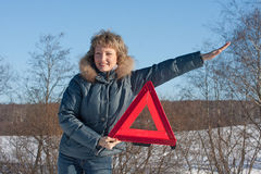 Woman with a warning triangle Royalty Free Stock Image