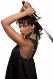 Woman warrior. Portrait of an attractive brunette woman wearing black holding samurai sword over head with serious expression over white Royalty Free Stock Images