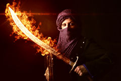 Woman warrior. Arabic Woman warrior with sword on fire against a dark background Stock Photos