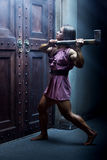 Woman warrior with axe. Standing at the door royalty free stock photo