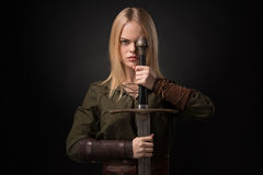Woman warrior with sword. In hand on gray background stock photo