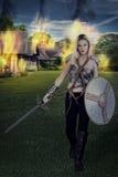 Woman warrior walking away from burning village Royalty Free Stock Image