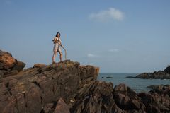 A woman with a staff on top of a rock. The conqueror of the mountain top. Royalty Free Stock Photo