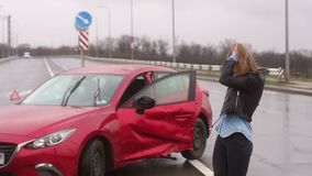 A woman was in an accident on the road in the rain, she is injured and scared. A young girl walks in the rain on an empty road near her broken car, she is stock footage