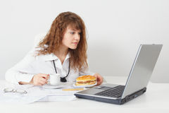 Woman was going to eat behind table at office. The young beautiful woman was going to eat behind a table at office stock image