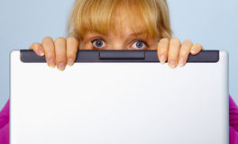 Woman was guilty and hides behind a computer. Frightened, the woman was guilty and hides behind a computer screen Stock Photography