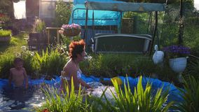 A woman was swimming in a small lake on a hot summer day. She jumps into the water, creates a splash of water. Garden. Happy holidays. A woman was swimming in a stock video footage