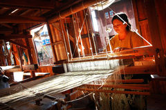 Woman was weaving silk fabric. INLE, MYANMAR - FEB 16: Unidentified woman was weaving silk fabric on Feb 16, 2011, Inle, Myanmar. Inle is famous for the tourism stock photography