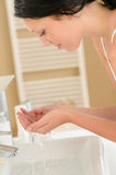 Woman wash face at basin bathroom Stock Images