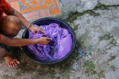 Woman wash hands dirty clothes in the basin black for cleansing. Thailand washing clothes style ancient and soak with detergent in the evening Royalty Free Stock Image