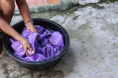 Woman wash hands dirty clothes in the basin black for cleansing. Thailand washing clothes style ancient and soak with detergent in the evening royalty free stock photography