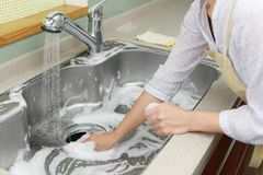 Woman wash the kitchen sink. Woman hands wash the kitchen sink stock photography