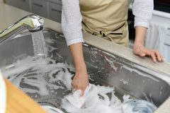 Woman wash the kitchen sink. Woman hands wash the kitchen sink royalty free stock photography