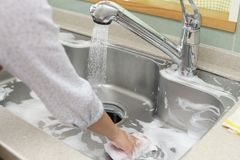 Woman wash the kitchen sink. Woman hands wash the kitchen sink royalty free stock image