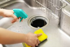 Woman wash the kitchen sink. Woman hands washing the kitchen sink royalty free stock photo