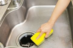 Woman wash the kitchen sink. Woman hands washing the kitchen sink royalty free stock image