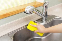 Woman wash the kitchen sink. Woman hands washing the kitchen sink royalty free stock photos