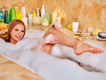 Woman wash leg in bathtube Stock Images